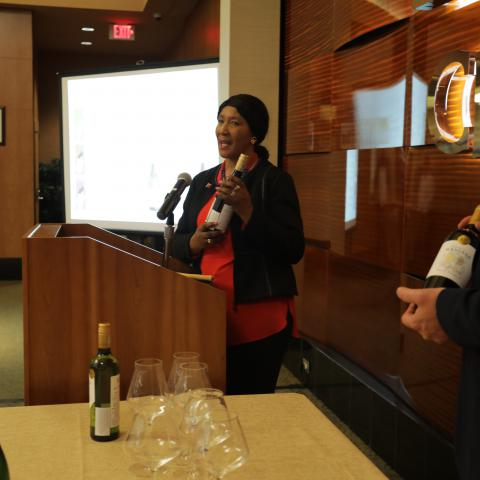Maki Mandela speaks at a podium holding a wine bottle from her House of Mandela collection