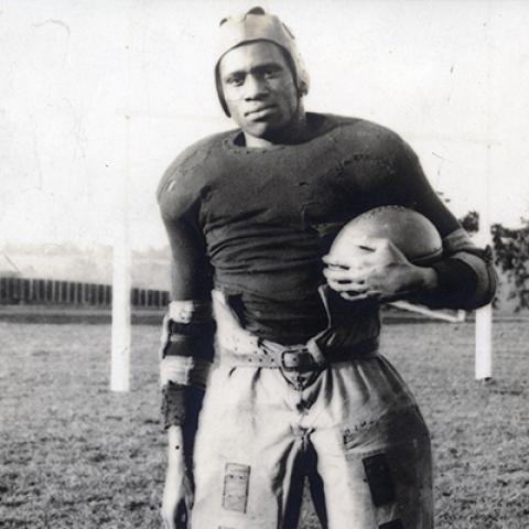 Paul Robeson standing with football in full uniform